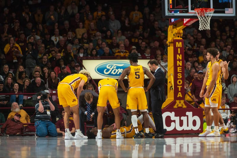 Gophers players surround Center Daniel Oturu as he lies on the floor after a foul at Williams Arena on Sunday, Jan. 12. Minnesota defeated Michigan 75-67. (Nur B. Adam / Minnesota Daily)