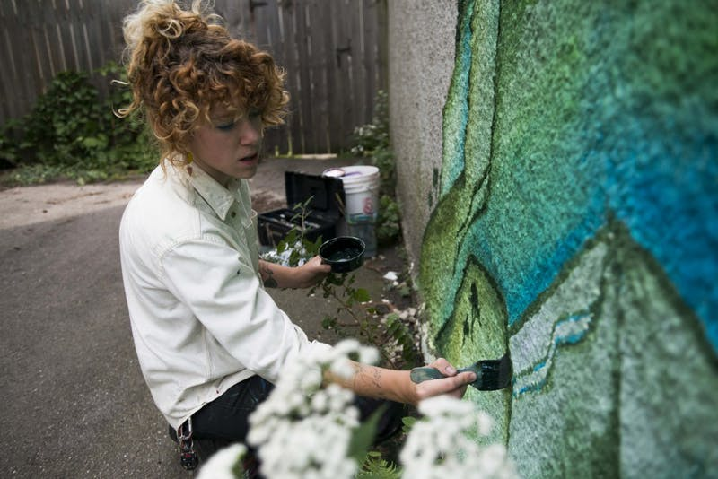 Liv Novotny paints a mural on the side of their garage in Minneapolis on Saturday, Sept. 7.