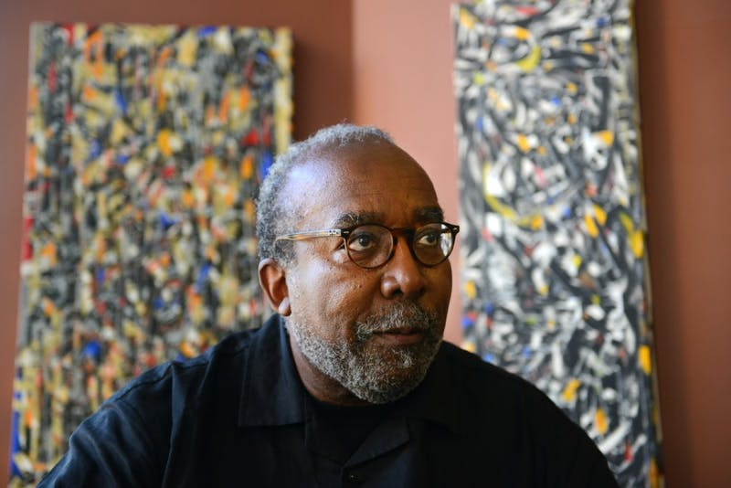 Twin Cities artist Ta–coumba T. Aiken poses with a selection of his rhythm paintings in the Show Gallery Lowertown on Tuesday. Aiken's exhibition opened to the public last night, November 4.