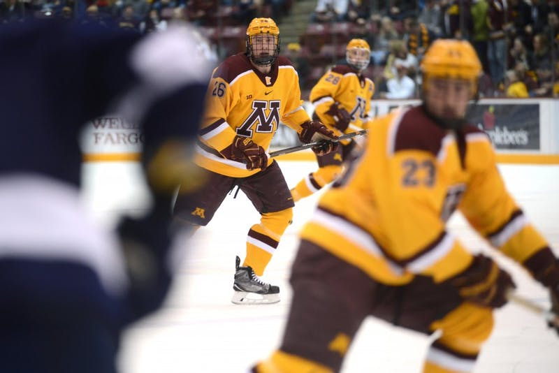 Forward Darian Romanko, center, eyes the puck during a game against Penn State at 3M at Mariucci Arena Feb. 4, 2017.