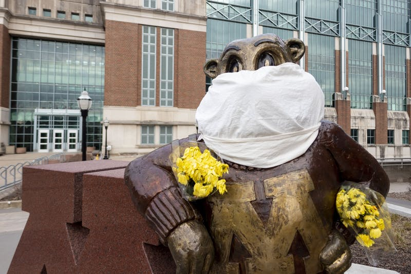 A cloth mask and bouquet of flowers are seen on the Goldy statue outside Coffman Memorial Union on Wednesday, April 1. (Parker Johnson / Minnesota Daily)