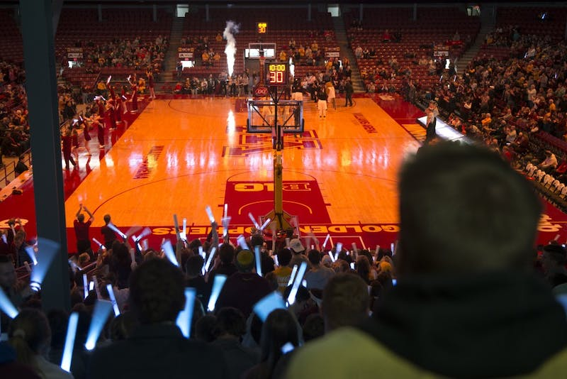 "Students hold light sticks for a ""light out"" before the women's basketball game against Wisconsin on Thursday.  University of Minnesota sororities asked members to attend the game to raise attendance and awareness of Gopher women's sports, with more than 300 attending in response."