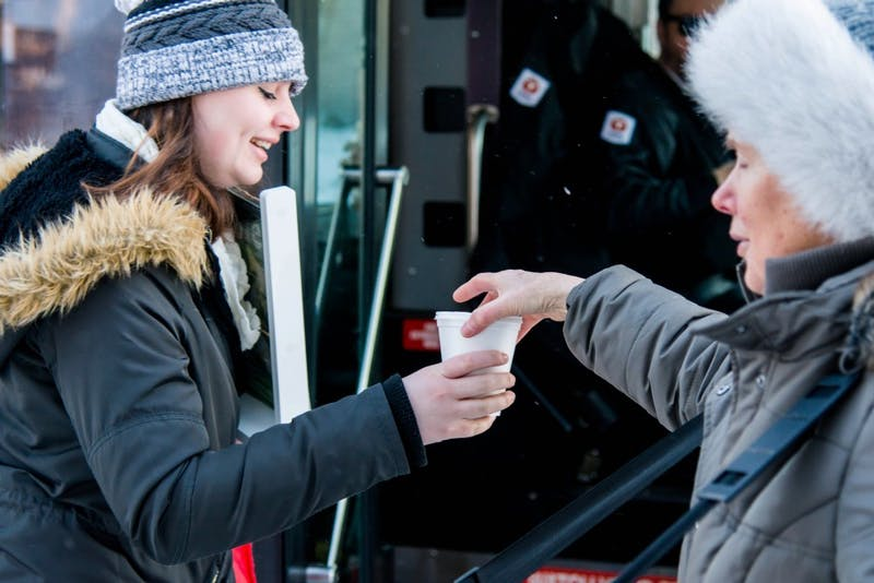 Shirley Arendt, right, offers a hot beverage and snacks to students in Como on Wednesday, Jan. 31. Every Wednesday morning, Arendt and other volunteers from Southeast Christian Church prepare and distribute coffee, hot chocolate and cookies to commuters and Como residents along 15th Avenue.