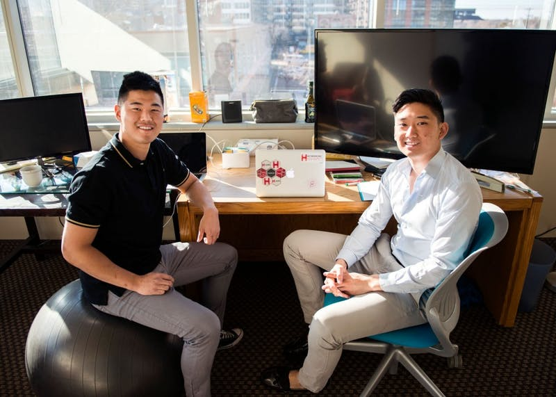 Homi CEO Philip Xiao, right, and Head of User Acquisition Greg Paik pose in their new office space in the Minnesota Supercomputer Building on Monday afternoon. Homi is a new start-up app that was designed to build relationships between students and alumni.