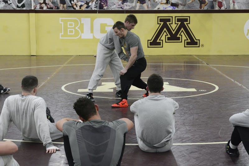 Tommy Thorn, left, demonstrates a move with Assistant Coach Dustin Schlatter, right, at the Bierman Athletic Building on Wednesday, Feb. 1, 2017.