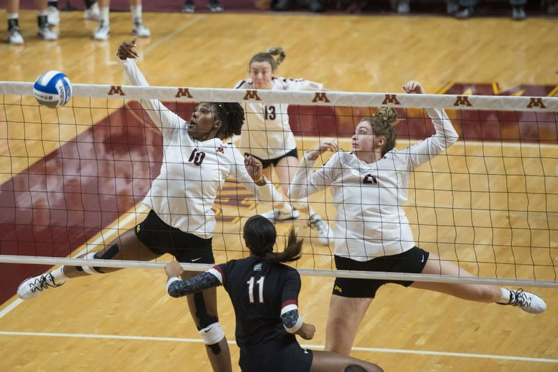 Stephanie Samedy and Regan Pittman block the ball at Maturi Pavilion on Saturday, Dec. 1, 2018.