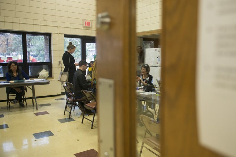 Election Judge Helen Torrens helps a voter through a window at the Van Cleve Park polling place on Tuesday, Nov. 6.