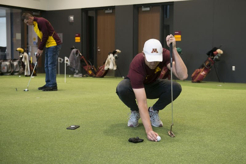 Junior Thomas Longbella lines up a shot on the putting green in the new indoor golf training facility on Monday, April 1. The facility borders the Les Bolstad Golf Course and allows for practice throughout winter months.