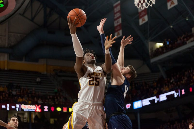 Gophers Center Daniel Oturu pushes past a defender for a layup at Williams Arena on Wednesday, Jan. 15.  Minnesota defeated the Penn State Nittany Lions 75-69. (Kamaan Richards / Minnesota Daily)