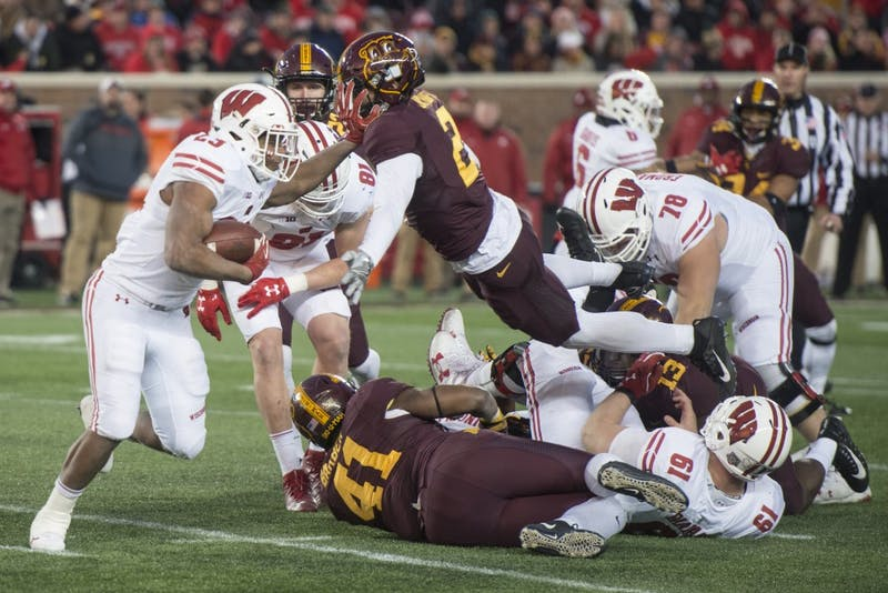 Wisconsin running back Jonathan Taylor stiff arms Gophers defensive back Jacob Huff at TCF Bank Stadium on Saturday, Nov. 25. The Badgers defeated the Gophers 31-0.