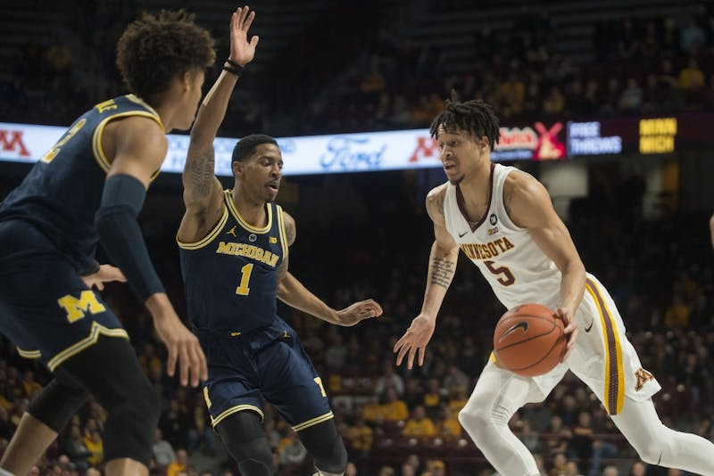 Junior Amir Coffey dribbles the ball across the court on Thursday, Feb. 21 at Williams Arena in Minneapolis. The Gophers lost to Michigan 69-60.