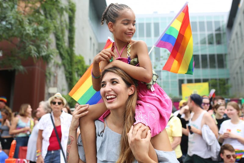 Natalie Deeble and daughter Saniya watch as the Pride Parade marches down Hennepin Ave in Minneapolis on June 24.