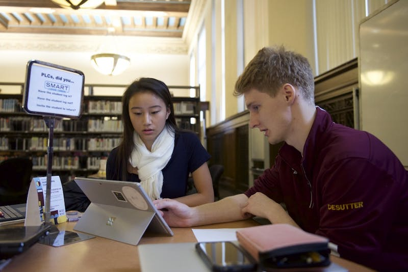 Tutor Noah DeSutter helps Sara Green at the SMART learning commons at Walter Library on Monday, Nov. 13.