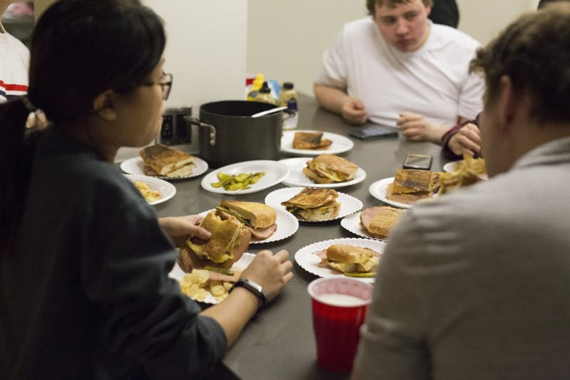 Members of the University of Minnesota's Cooking Club gather outside the kitchen in Coffman Union to enjoy the cuban club sandwiches they prepared together.