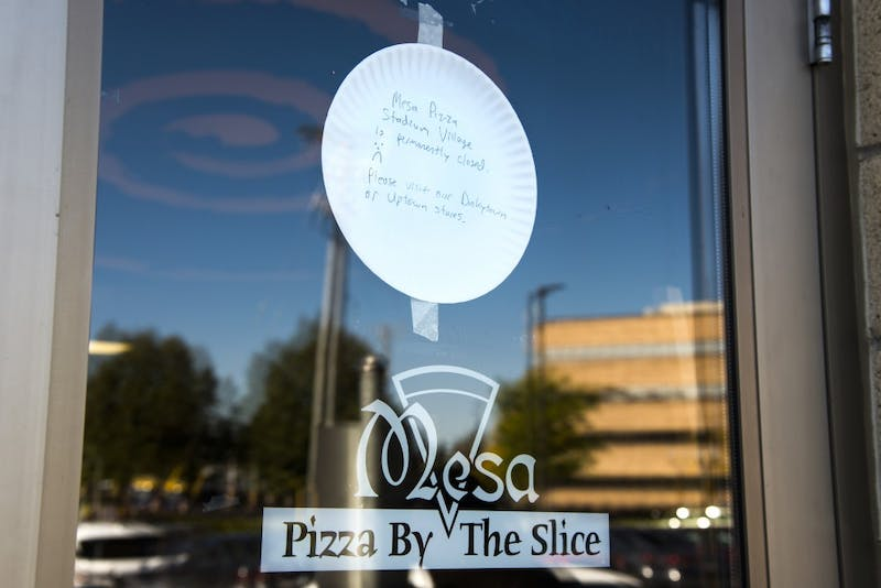 """A paper plate reading """"Mesa Pizza Stadium Village is permanently closed"""" hangs taped to the door of the Stadium Village Mesa Pizza location on Sunday."""