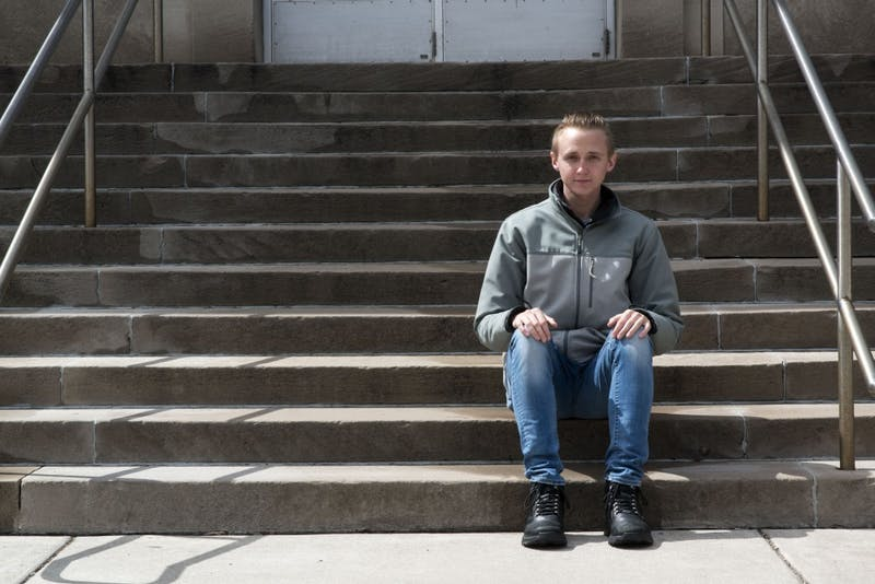 "Blake Downing poses for a portrait outside Appleby Hall on Saturday, April 13. Downing lost his mother when he was 14 which impacted his mental health when he moved to a new high school and eventually away from home to attend the University of Minnesota. He now meets regularly with seven other students in Appleby Hall as part Student Counseling Services which helped introduce a support system into Downing's life that he says has been ""life changing."""