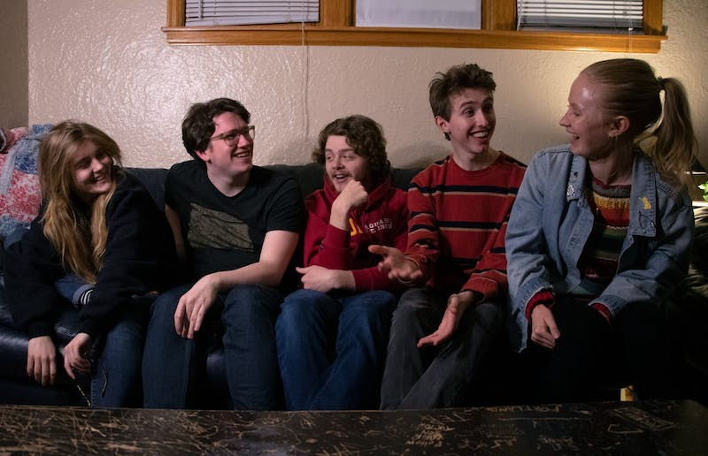 """From left, Izzy Bobby, Carter Ridl, Jacob Mechler, Henry Kueppers and coach Summer Freed of MN long form improv team """"Robot Family Band"""" laugh while posing for a portrait before their team practice on Wednesday, March 4. The team won the Upper Midwest Regional Championship for long form improv, and is now advancing to nationals."""