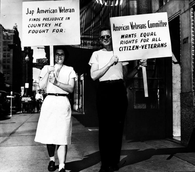 Protesters hold signs criticizing racially restrictive housing codes in Minneapolis in 1946.