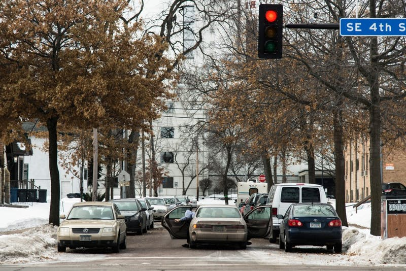 Sunday morning church goers exit their vehicle  on a nearly-full section of 4th Ave SE in Marcy-Holmes, Sunday, Jan. 28. The Church of Minneapolis, along 4th Street SE has had issues with members finding parking in the neighborhood.