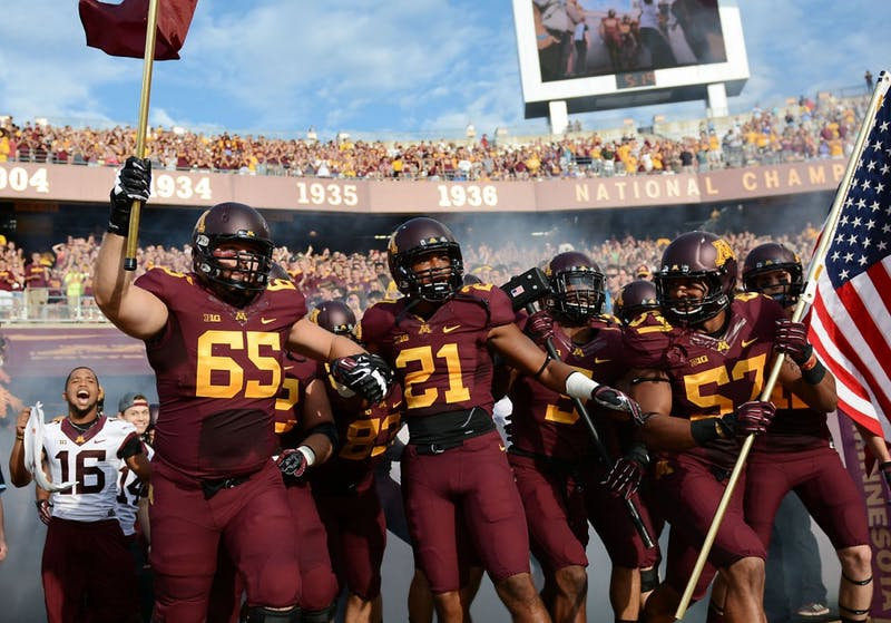 Minnesota players charge onto the field before the start of the Gophers' season opener against UNLV on Thursday at TCF Bank Stadium.