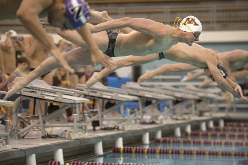 Junior Bowen Becker dives off the blocks at the start of the men's 400 yard freestyle relay at the Jean K. Freeman Aquatics Center on Saturday, Jan. 27, 2018.