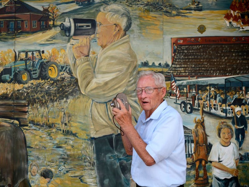 Billy Thompson stands with his camera in front of a mural in downtown Milan on July 25. The mural depicts Thompson documenting Milan's history, something he strives to do each day.