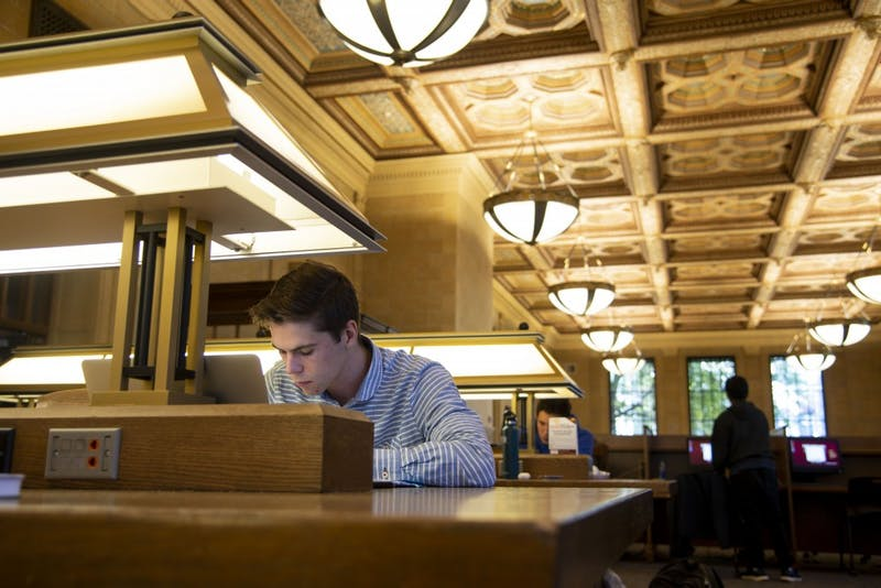 Sophomore Bradley Hartwyk works on an assignment in Walter Library on Friday, Oct. 26. The University's decision to transition lights to LEDs in heavy-traffic buildings is one initiative driven by its goal of eliminating 100 percent of carbon emissions by 2050. (Mrunal Zambre / Minnesota Daily)