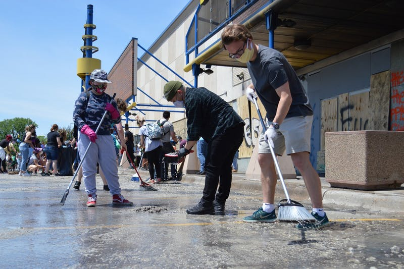 Jackson Hampton, right, works near the Hi-Lake Shopping Center in East Lake Street, just a few blocks from the Minneapolis Third Police Precinct, to help clear debris from the burned-down businesses on Sunday, May 31.