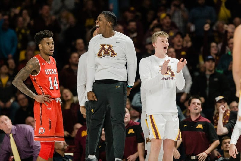 Marcus Carr celebrates on the bench with his Gophers teammates in a game against Utah.