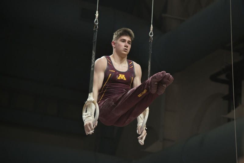 Freshman David Pochinka competes in the still rings at Maturi Pavilion on Saturday, Jan. 26.