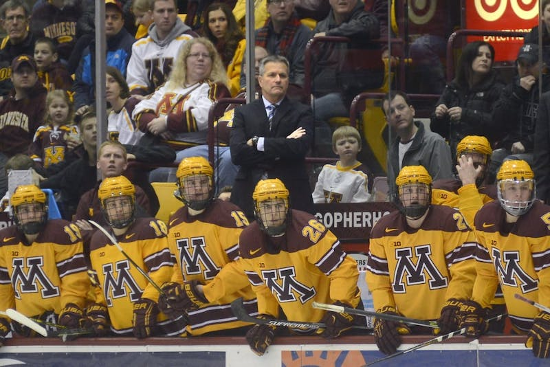 Gophers players and head coach Don Lucia follow the game at 3M Arena at Mariucci on Saturday, Feb. 7, 2015.