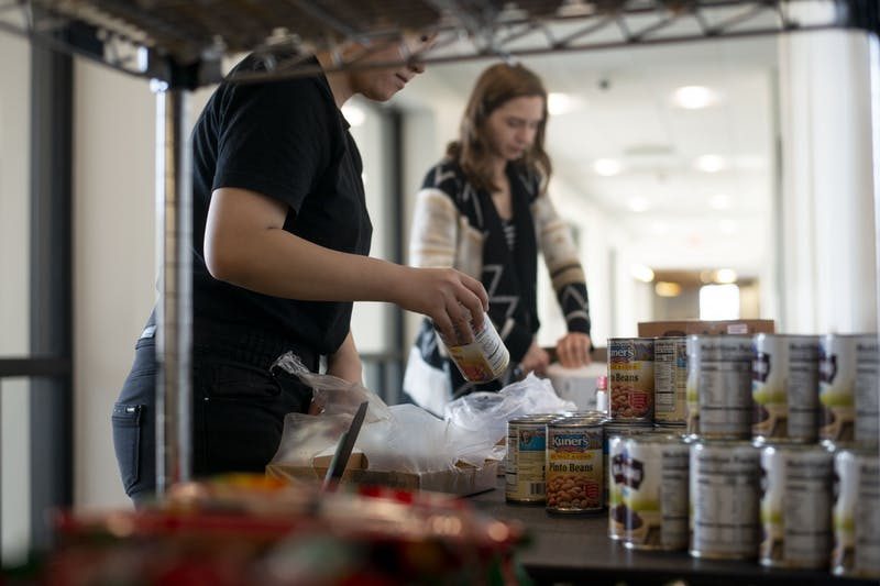 Volunteers Amber Chang, left, and Merri Bonde, right, prepare the Nutritious U Food Pantry to open in Coffman Union on Tuesday, Oct. 29.