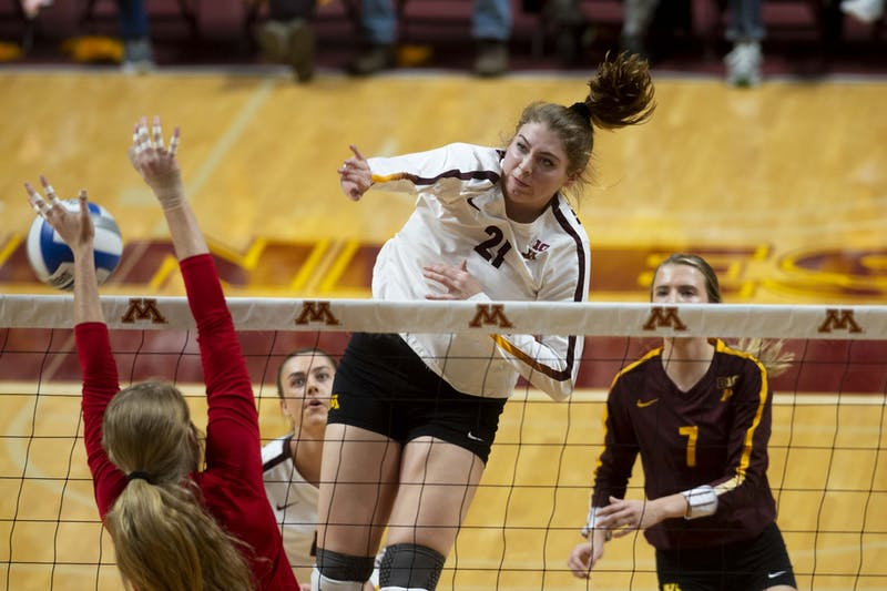 Middle Blocker Regan Pittman jumps to spike the ball at the Maturi Pavilion on Friday, Nov. 22. The Gophers took Nebraska to five sets but ultimately fell 3-2.