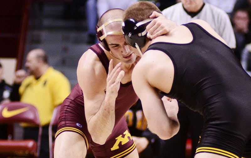 Minnesota's Cody Yohn (left) attempts to take down Iowa's Nick Moore on Saturday, Jan. 26, 2013, at Williams Arena.