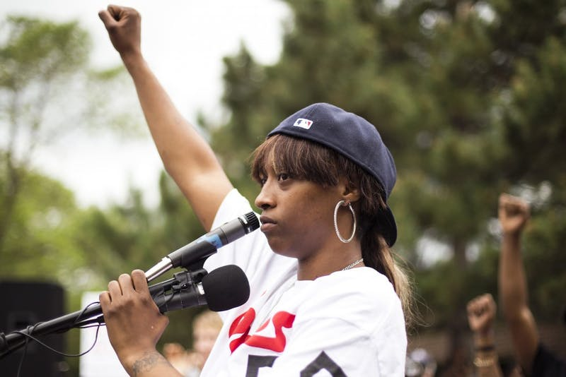 Diamond Reynolds stands with a raised fist after speaking to a vast crowd that gathered outside of the J.J. Hill Montessori School in St. Paul on Thursday. Philando Castile was an employee of the school, where he worked as a cafeteria supervisor.