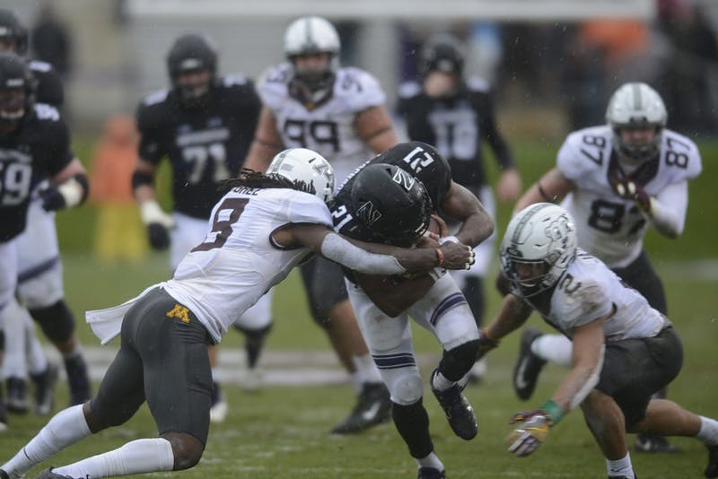 Eric Carter and Jacob Huff tackle Northwestern running back Justin Jackson on Saturday Nov. 18 at Ryan Field in Evanston, Illinois.