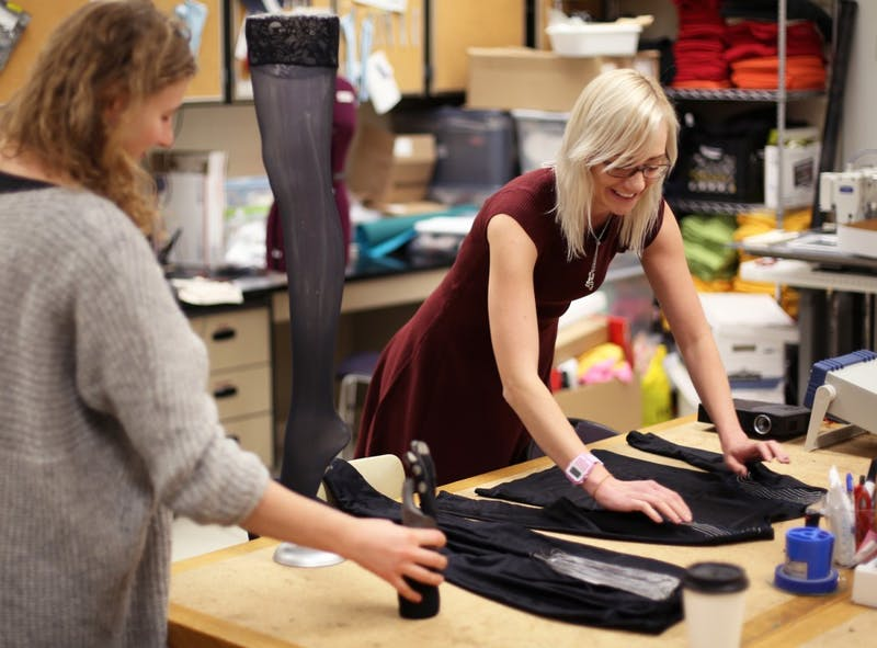 """Grad students Julia Duvall (left) and Crystal Compton (right) organize several of their wearable technology garments. One of Duvall and Compton's pieces , named """"Brace Yourself - World's Sexiest Knee Brace"""", is a technologically advanced tight that prevents harmful knee movements by retraining the muscles."""