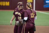 Juniors Katelyn Kemmetmueller and Amber Fiser celebrate after an out on Saturday, May 18 at the Jane Sage Cowles Stadium in Minneapolis. The Gophers beat the University of Georgia 2-1.