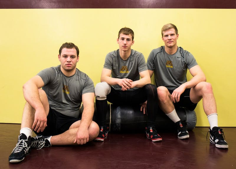 Minnesota wrestlers, left to right, Michael Kroells, Tommy Thorn and Brett Pfarr pose for a portrait together before their practice in the Bierman Field Athletic Building on Tuesday. The trio have a combined duals record of 43-8.