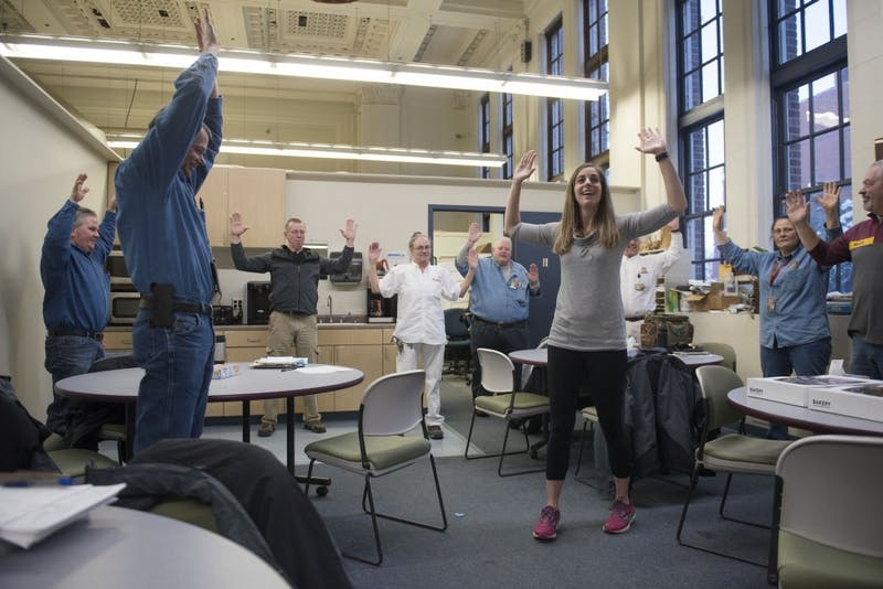 Andrea Santi leads University Facilities Management employees in pre-shift stretch on Friday, Feb. 15. The program was started by Santi and fellow graduate student Nael Banat as part of their Kinesiology studies.