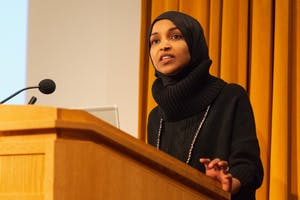 """Rep. Ilhan Omar addresses an audience in Cowles Auditorium on Tuesday, Feb. 18. The event centered around her """"Pathway to Peace,"""" a package of seven bills which aim to reorient U.S. foreign policy."""