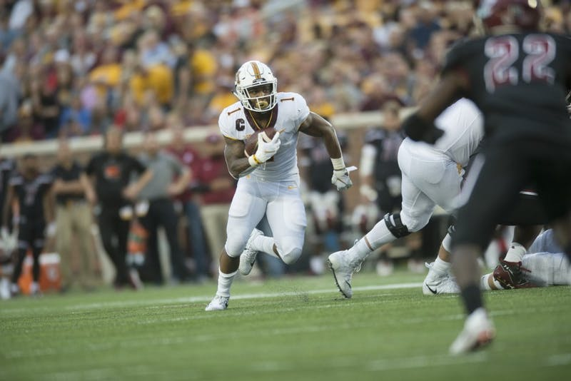 Running back Rodney Smith faces oncoming tackles as his team mates make a path during the game against New Mexico on Thursday, Aug. 30 at TCF Bank Stadium.