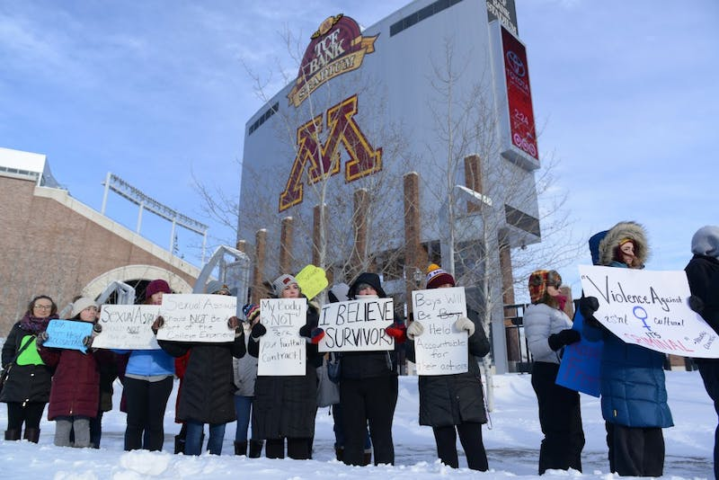 Protesters stand in front of TCF Bank Stadium on Sat. Dec. 17, 2016. After 10 Gopher's football players were suspended for sexual assault, the Gopher's football team boycotted playing in the holiday bowl until the suspensions were lifted.