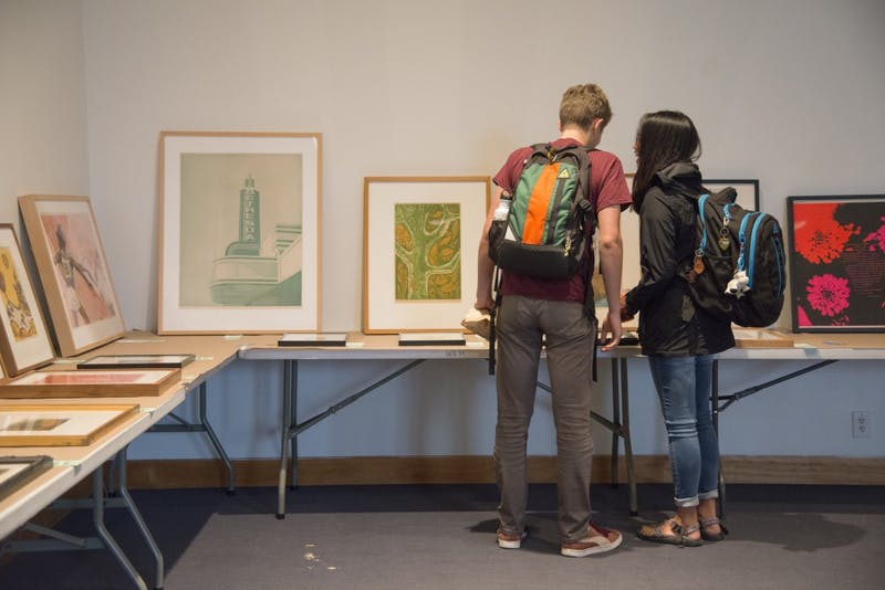 Two students look at the art available to rent on Wednesday, Sept. 19, at Weisman Art Museum. The museum held an art rental event where students could study, eat snacks and find affordable art to rent or purchase.