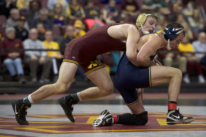 Senior Nick Wanzek at 165 wrestles with No. 5 Logan Massa during the dual against Michigan on Sunday. The Gophers lost to Michigan, their first loss of the season.