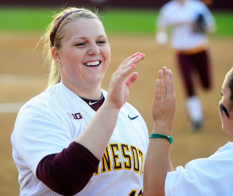 Sophomore pitcher Sara Groenewegen high-fives her teammates while returning to the dugout at the Jane Sage Cowles Stadium on Friday evening against Purdue.