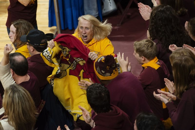 "Fans cheer for the ""blanket lady"" as she runs through the Maturi Pavilion on Friday, Nov. 30. The Gophers swept Bryant three sets to none as a start to their postseason."