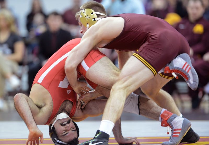 Nebraska's Dustin Williams is flipped by junior Nick Wanzek at the Sports Pavilion on Friday, Jan. 20. The Gophers lost 11-21 against  Nebraska.