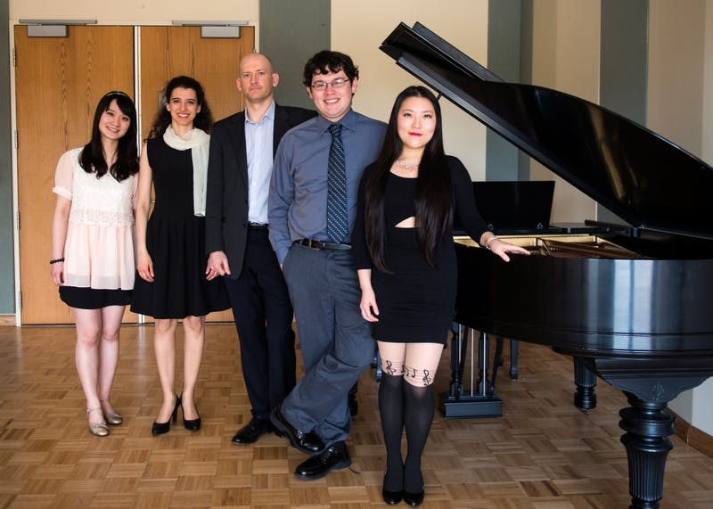 Left to right, graduate students Nai-Cha Chen, Maria Mannone, Nathaniel Akers, William Heinze and Yan Pang pose in a rehearsal room in Ferguson Hall on Saturday afternoon. They will be performing their Composition Recital this Friday to present their original works.