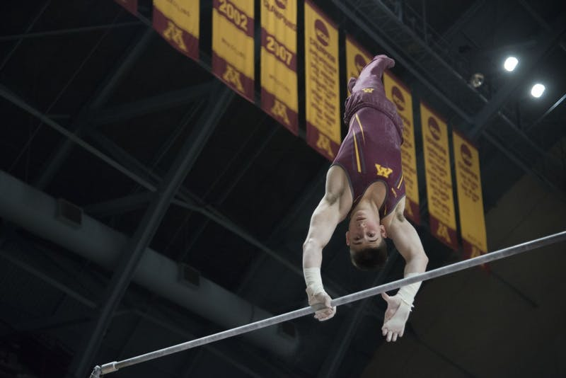 Freshman David Pochinka competes in the horizontal bar at Maturi Pavilion on Saturday, Jan. 26.